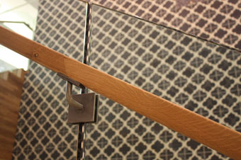 IMS developed handrail brackets that can be mounted at the seams between the sheets of glass.